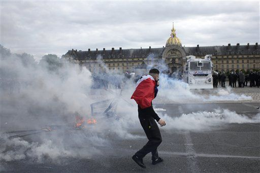 A demonstrators stands among tear gas during a demonstration at the Place des  Invalides in Paris Tuesday, June 14, 2016. Protesters in Paris threw projectiles at police officers, who responded with tear gas, amid demonstrations by tens of thousands of people opposed to a proposed labor law.