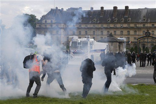 Protestors walk among tear gas canisters during demonstration in Paris, Tuesday, June 14, 2016. Protesters in Paris threw projectiles at police officers, who responded with tear gas, amid demonstrations by tens of thousands of people opposed to a proposed labor law.