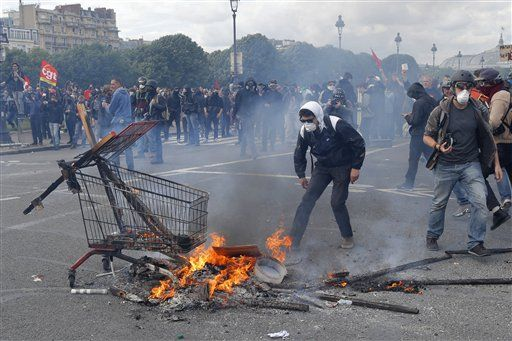 Youth burn sticks and items during demonstration scene in Paris, Tuesday, June 14, 2016. Protesters in Paris threw projectiles at police officers, who responded with tear gas, amid demonstrations by tens of thousands of people opposed to a proposed labor law.