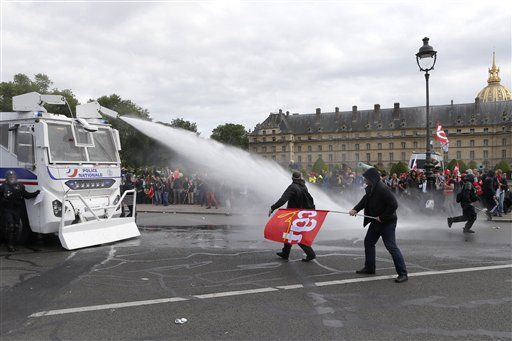 Police forces use a water canon on protestors during demonstration scene in Paris, Tuesday, June 14, 2016. Protesters in Paris threw projectiles at police officers, who responded with tear gas, amid demonstrations by tens of thousands of people opposed to a proposed labor law.