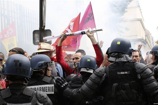 A demonstrator faces riot police officers during a demonstration in Paris Tuesday, June 14, 2016. Protesters in Paris threw projectiles at police officers, who responded with tear gas, amid demonstrations by tens of thousands of people opposed to a proposed labor law.