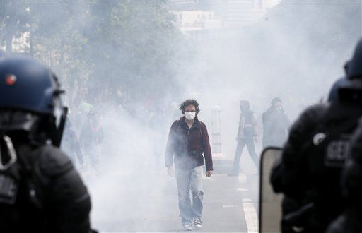 A demonstrators wears a mask during a demonstration in Paris Tuesday, June 14, 2016. Protesters in Paris threw projectiles at police officers, who responded with tear gas, amid demonstrations by tens of thousands of people opposed to a proposed labor law.