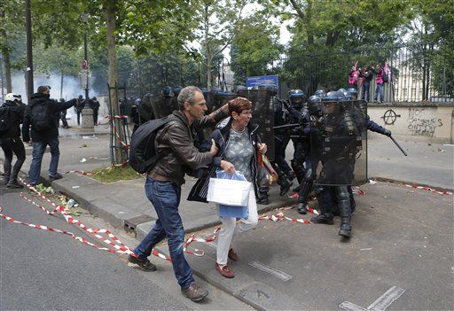 A man protects a woman in front of riot police officers during a demonstration in Paris Tuesday, June 14, 2016. Street protests are planned across France, rail workers and taxi drivers are going on strike and the Eiffel Tower is due to be closed as part of a protest against a reform aimed at loosening the country's labor rules.