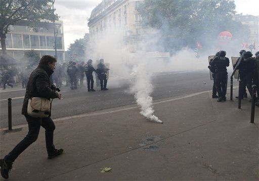 A man walks past a gas canister during a demonstration in Paris Tuesday, June 14, 2016. Street protests are planned across France, rail workers and taxi drivers are going on strike and the Eiffel Tower is due to be closed as part of a protest against a reform aimed at loosening the country's labor rules.