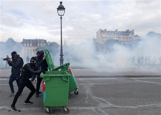 Youth use trash bins during a demonstration on the Place des Invalides in Paris, Tuesday, June 14, 2016. Protesters in Paris threw projectiles at police officers, who responded with tear gas, amid demonstrations by tens of thousands of people opposed to a proposed labor law.