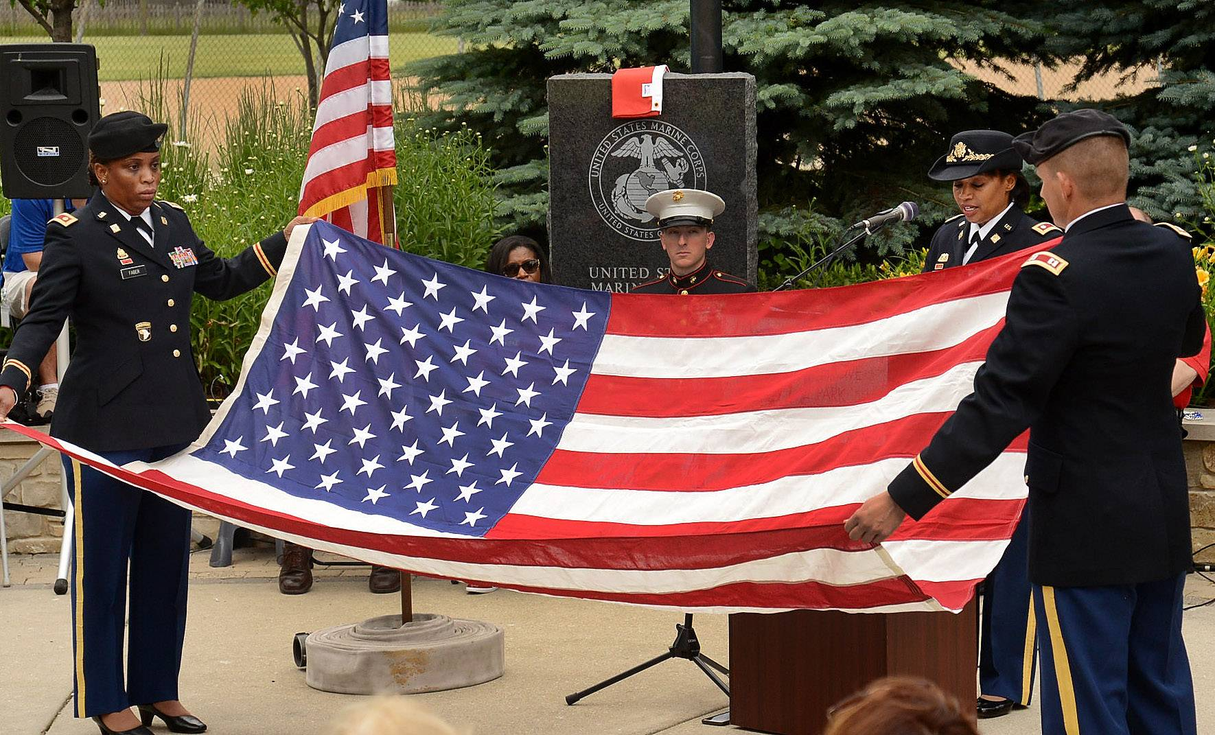 Major Erna M. Faber, left, and reservist Jason Smigelski, both from the 85th Army Reserve Support Command in Arlington Heights flank the American flag on Tuesday evening as Lt. Col. Priscilla Van Zanten speaks about the meaning of the flag during Buffalo Grove Park District's annual Flag Day celebration at Veterans Park.