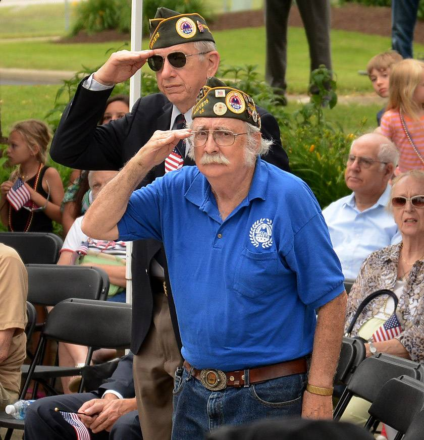 Vietnam veteran and Wheeling resident Robert Blocks, foreground, salutes the raising of the Marine flag on Tuesday during the Buffalo Grove Park District's annual Flag Day celebration at Veterans Park.
