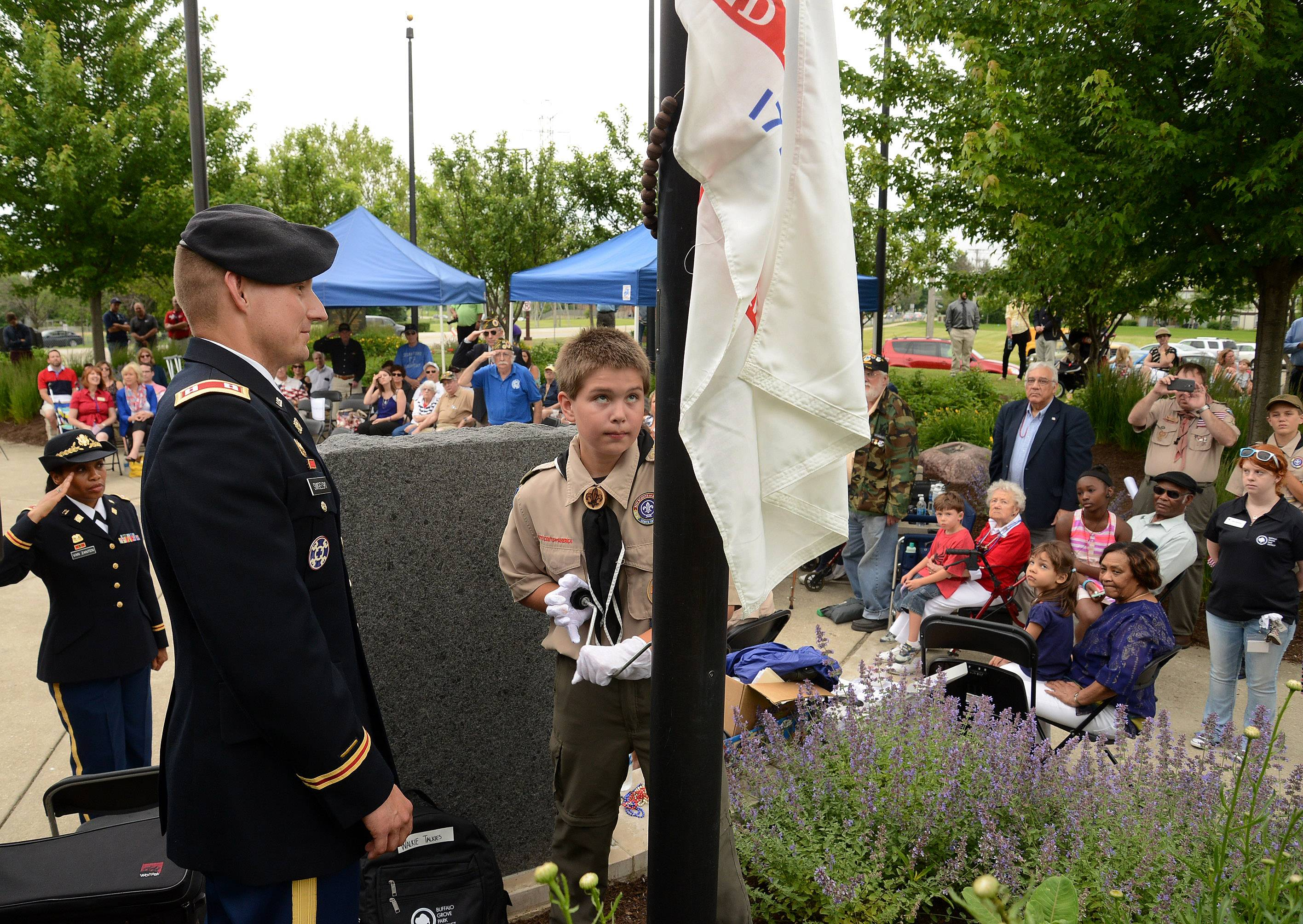Reservist Jason Smigelski of the 85th States Army Reserve Support Command in Arlington Heights and Boy Scout Jacob Hammon of Troop 79 raise the flag of the Army during the Buffalo Grove Park District's annual Flag Day celebration at Veterans Park.