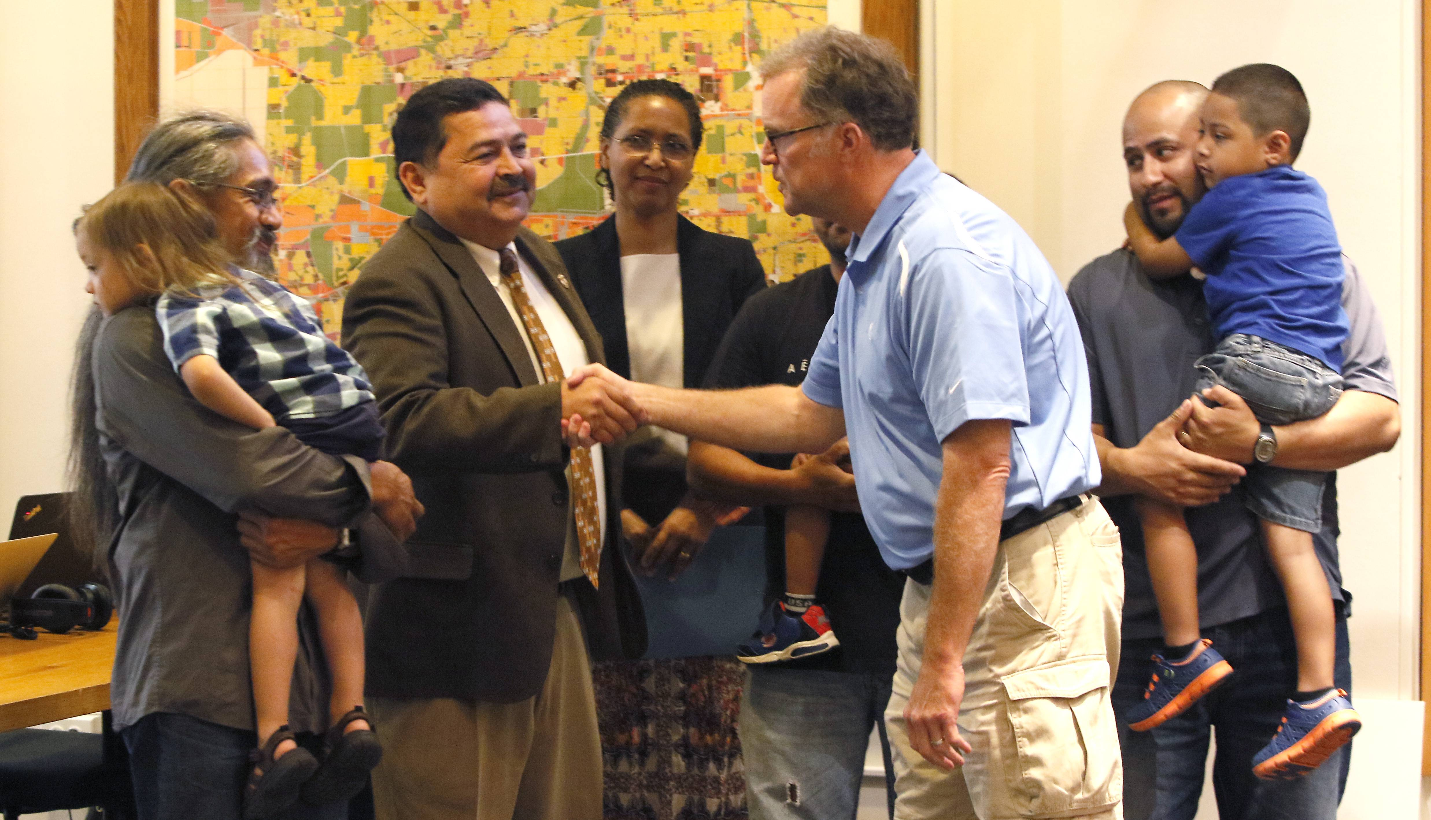 West Chicago Mayor Ruben Pineda, left, shakes hands with DuPage County Board Chairman Dan Cronin, right, after the county board honored several West Chicago families for participating in the Fathers Reading Every Day program offered by West Chicago Elementary District 33.