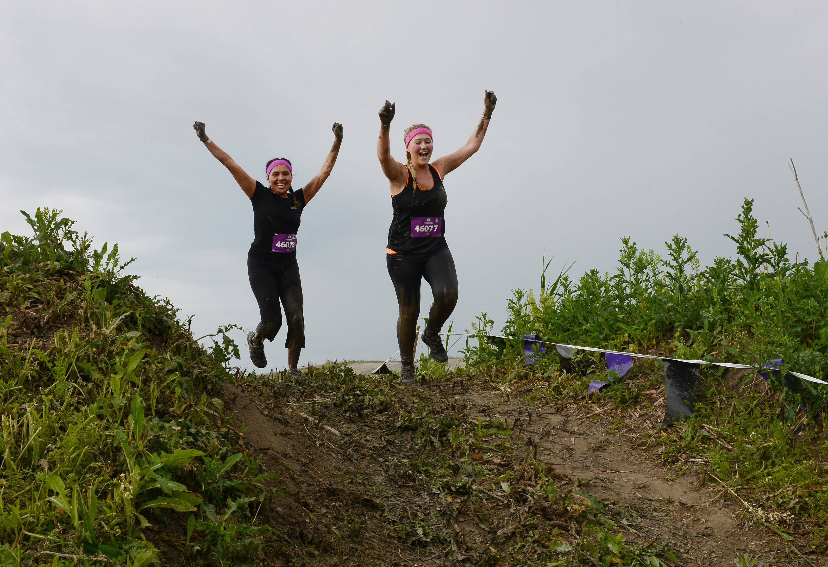 Kate Dominguez, left, and Brentney Hutchinson, both of Chicago, celebrate as they reach the top of a hill during the Chicago Women's Mudderella at the Lake County Fairgrounds in Grayslake Saturday.
