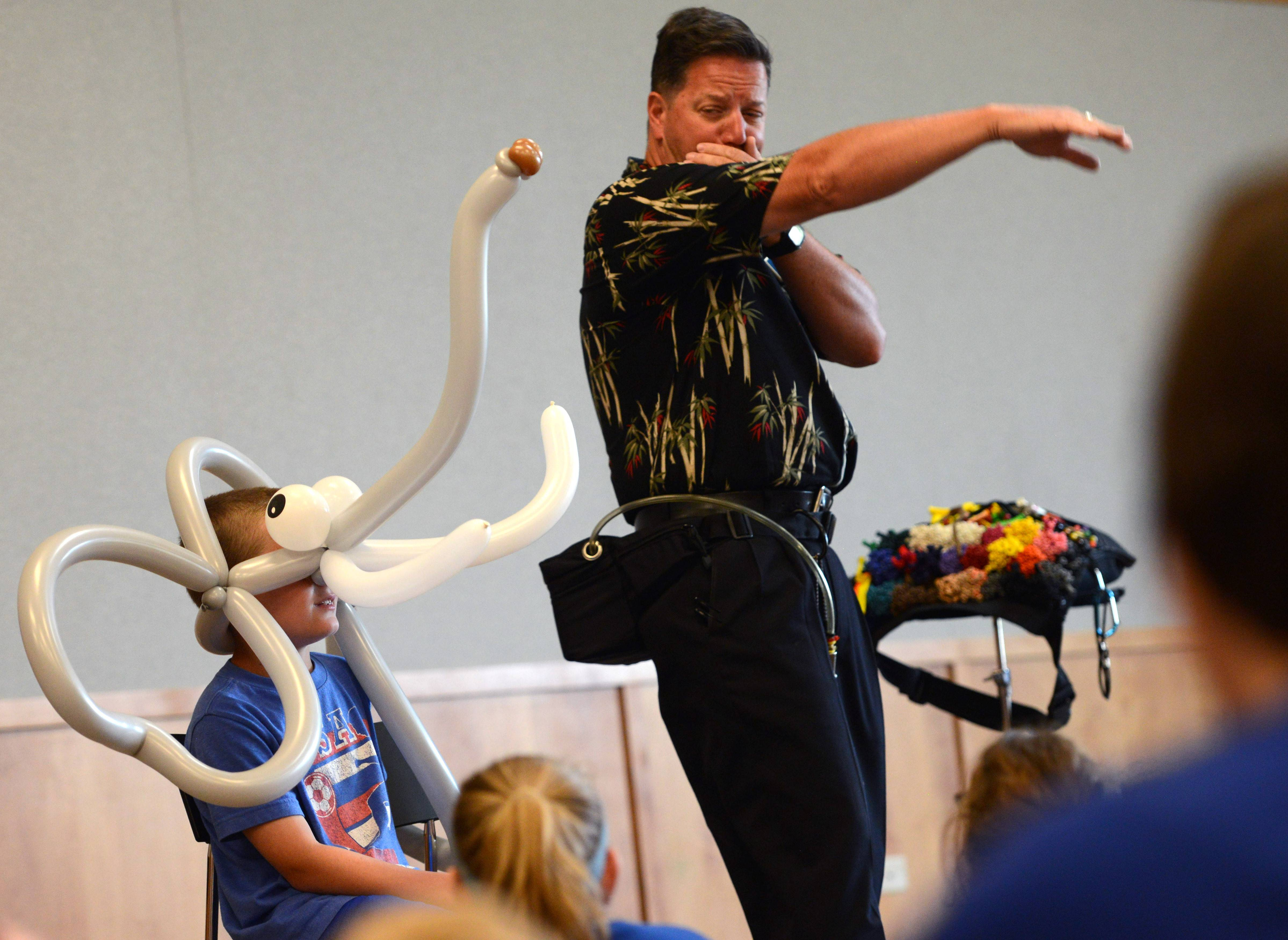 Ben Michels, 8, of Lake Zurich, and balloon artist Dale Obrochta imitate elephants Monday during Obrochta's improvisational balloon show at the Ela Area Public Library in Lake Zurich.