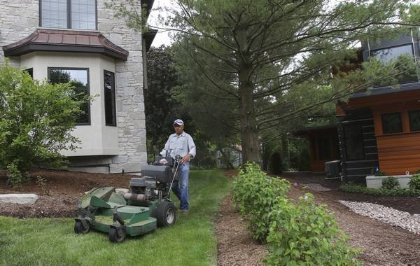 A worker with C.B. Conlin Landscaping, Inc. in Naperville mows a  residential lawn in - Suburban Summer Debate: When Is Lawn Mowing OK?