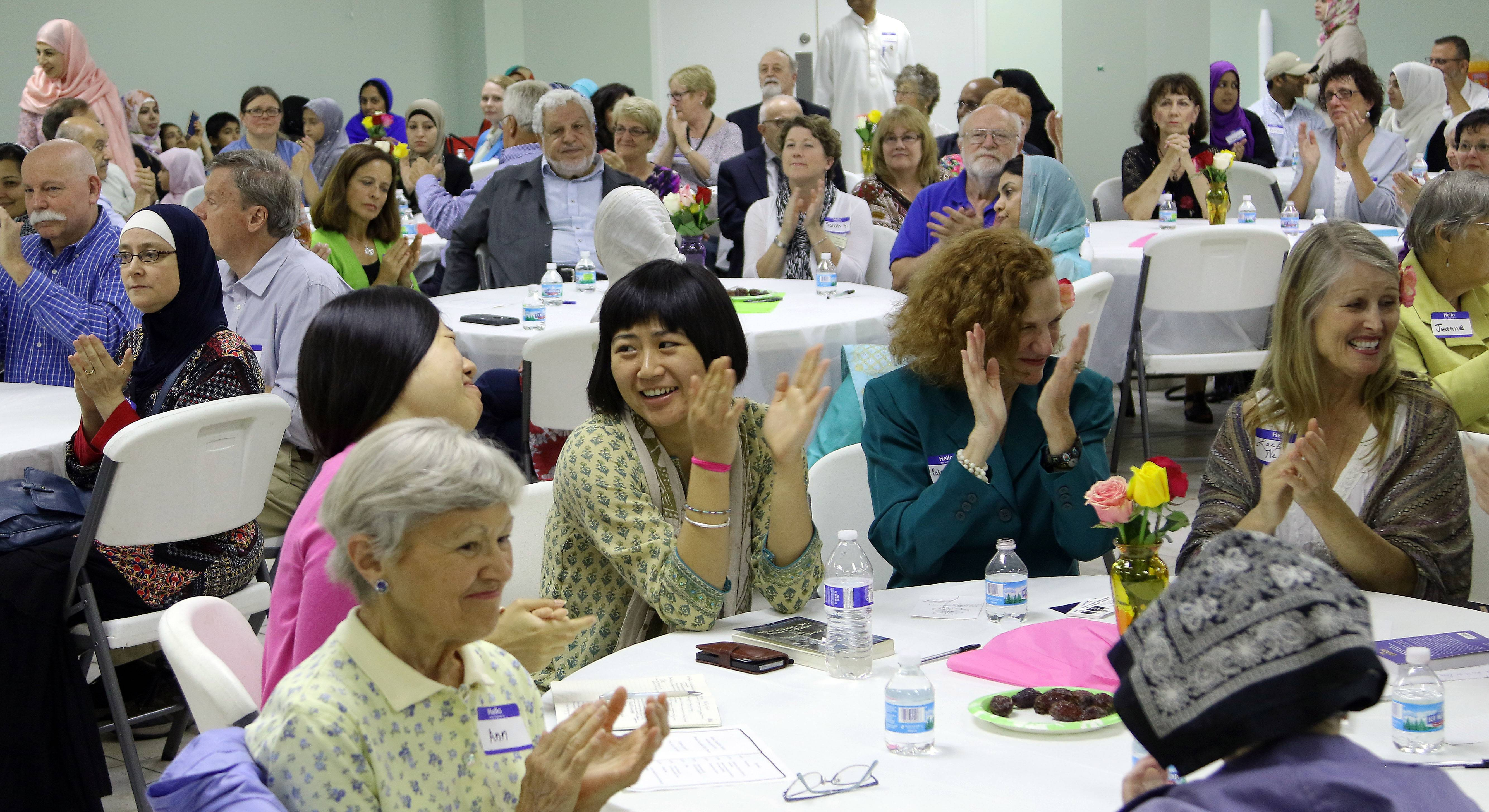 Attendees applaud remarks made during Wednesday's interfaith dinner at Islamic Foundation North in Libertyville.