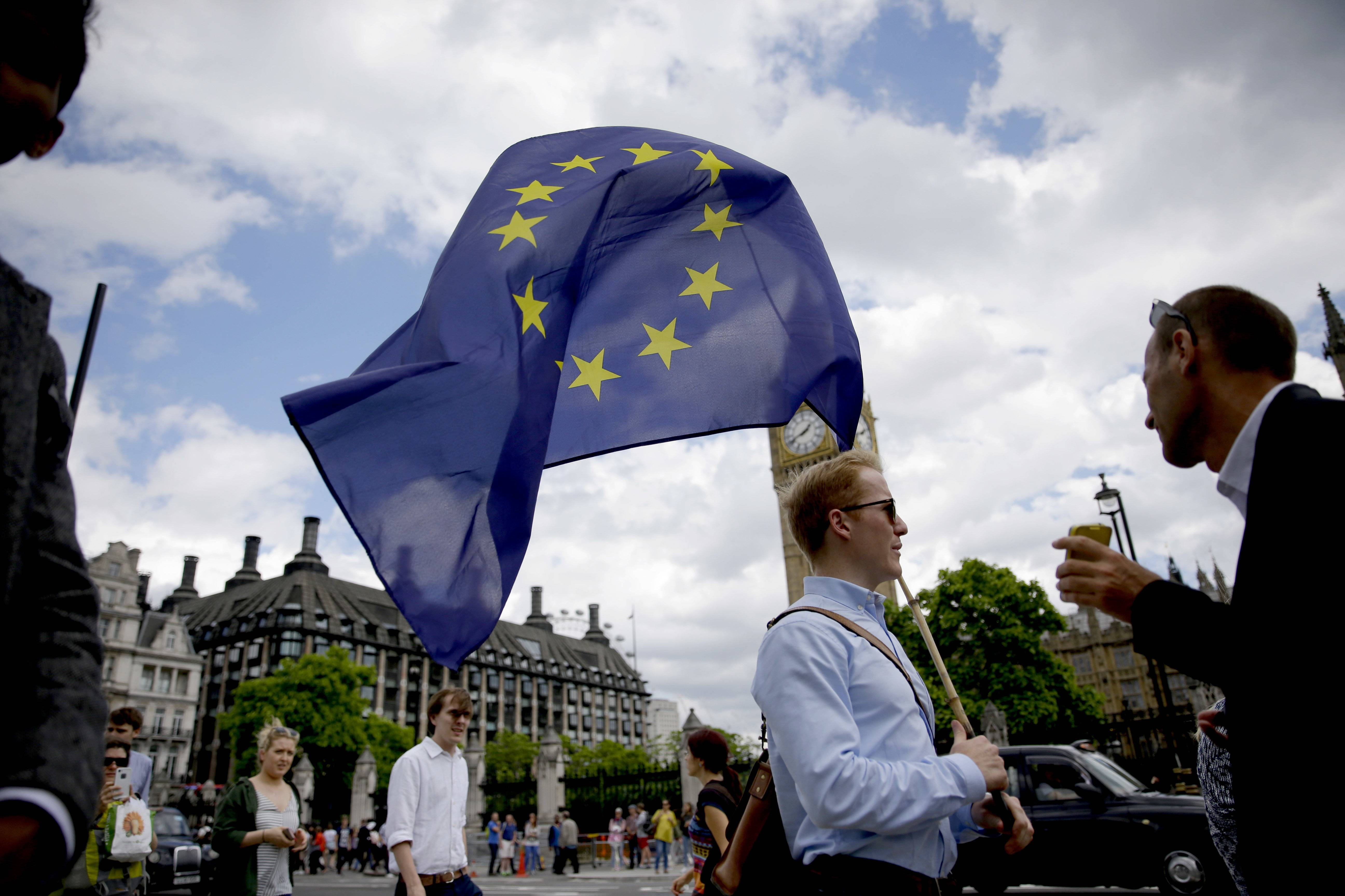 A remain supporter stops to talk to people as he walks around with his European flag across the street from the Houses of Parliament in London, Friday, June 24, 2016. Britain's Prime Minister David Cameron announced Friday that he will quit as Prime Minister following a defeat in the referendum which ended with a vote for Britain to leave the European Union.