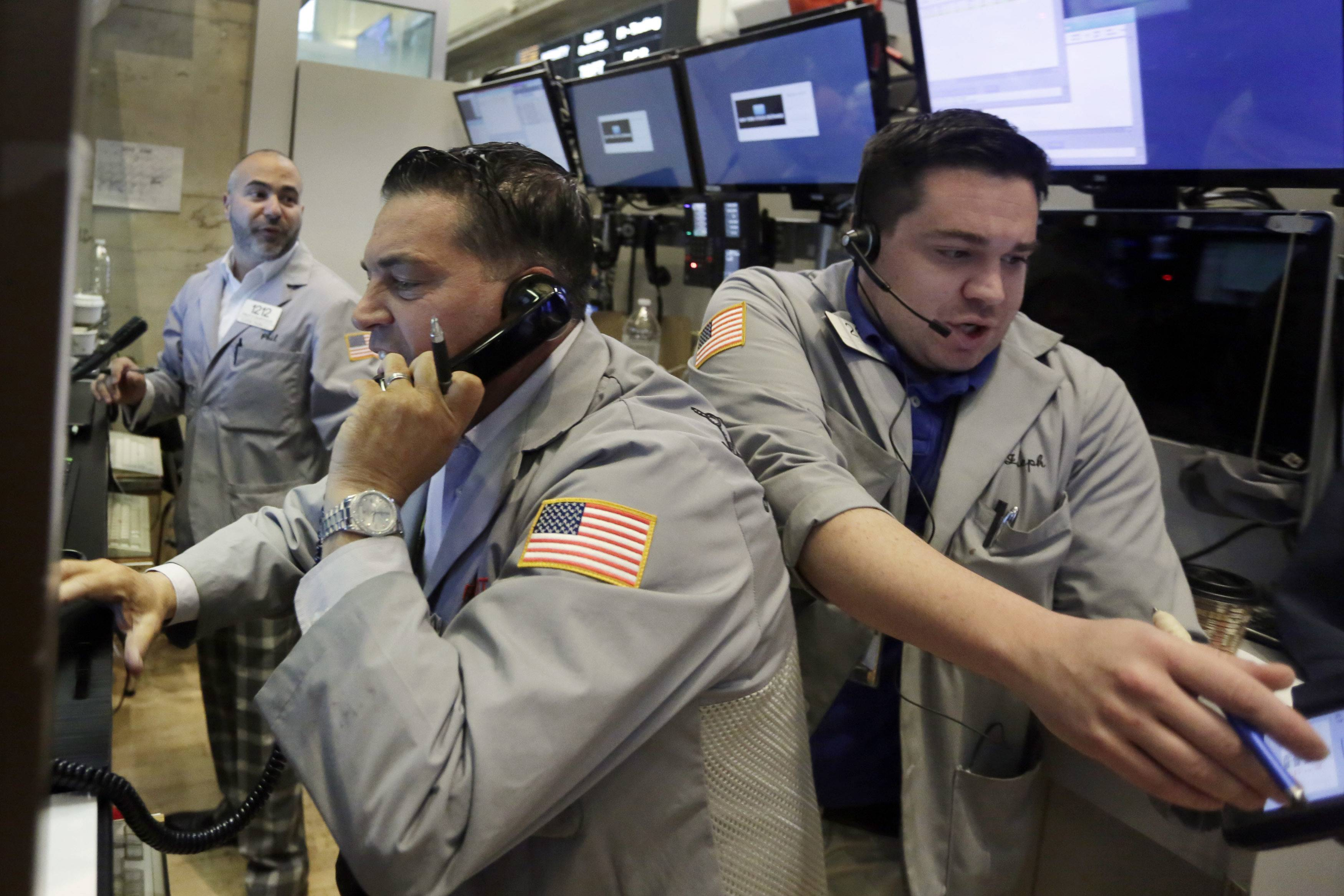 Traders Jonathan Mueller, center, and Joseph Lawler, right, work on the floor of the New York Stock Exchange, Friday, June 24, 2016. U.S. stocks are plunging after Britons voted to leave the European Union.