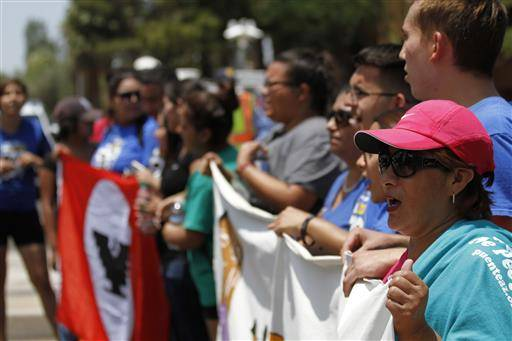 Activists stand in the middle of a major downtown road to protest a Supreme Court decision on immigration Thursday June 23, 2016, in Phoenix. The crowd carried signs in sweltering heat and chanted in Spanish and English. About two dozen more stood on the sidewalk in the shade. (AP Photo/ Beatriz Costa-Lima)