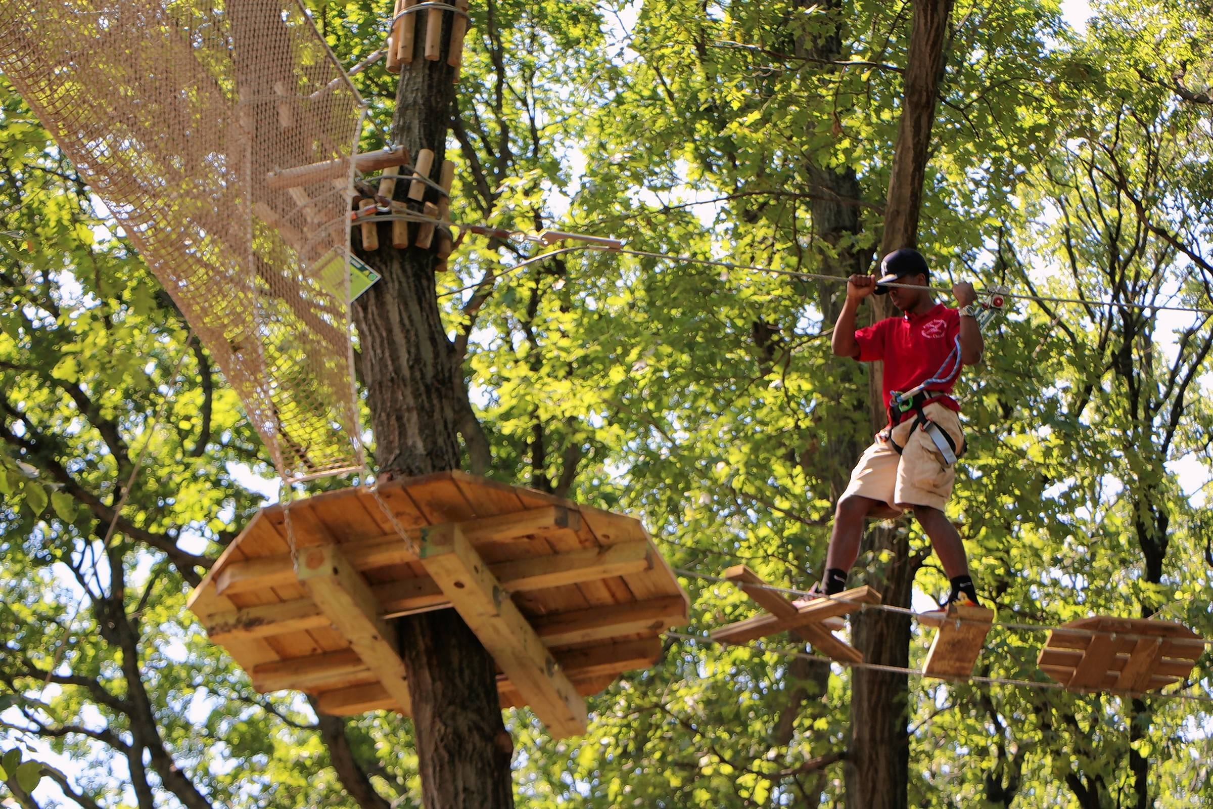 Kinnard Hughes of Chicago demonstrates the obstacle course at the Go Ape treetop adventure area in Bemis Woods South in Western Springs during a press preview Friday.