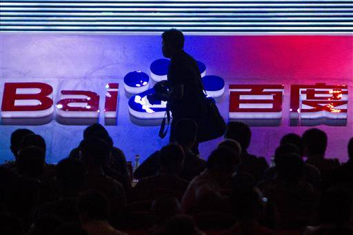 FILE - In this Sept. 2, 2011 file photo, a photographer walks past the logo of Baidu Inc., which operates China's dominant search engine, during a technology innovation conference held by the company at China's National Convention Center in Beijing, China. China issued new regulations on Saturday, June 25, 2016 demanding search engines clearly identify paid search results, months after a terminally-ill cancer patient complained that he was misled by the giant search engine Baidu. (AP Photo/Alexander F. Yuan, File)