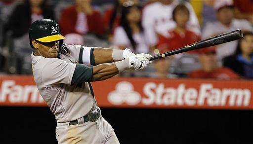 Oakland Athletics' Khris Davis hits a three-run home run against the Los Angeles Angels during the eighth inning of a baseball game in Anaheim, Calif., Friday, June 24, 2016. (AP Photo/Alex Gallardo)