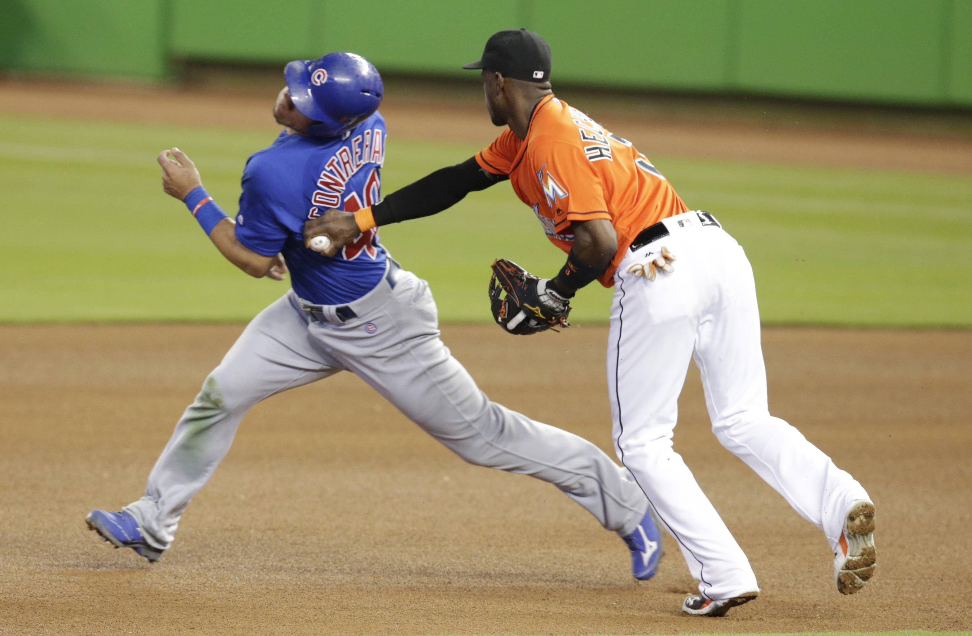Chicago Cubs' Willson Contreras, left, is tagged out by Miami Marlins shortstop Adeiny Hechavarria on an attempt to steal second during the fourth inning of a baseball game, Sunday, June 26, 2016, in Miami.