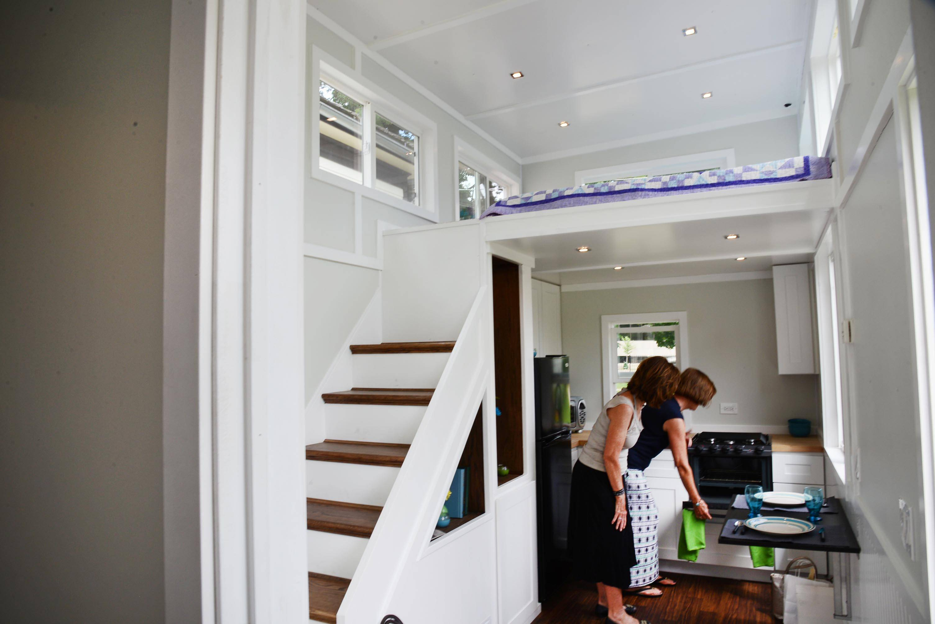 Jan Pohl and Nellie Patterson of Arlington Heights look at the kitchen area of a 250-square-foot tiny house on display Sunday during the Arlington Heights Historical Society's annual House Walk. Above them is the bedroom.