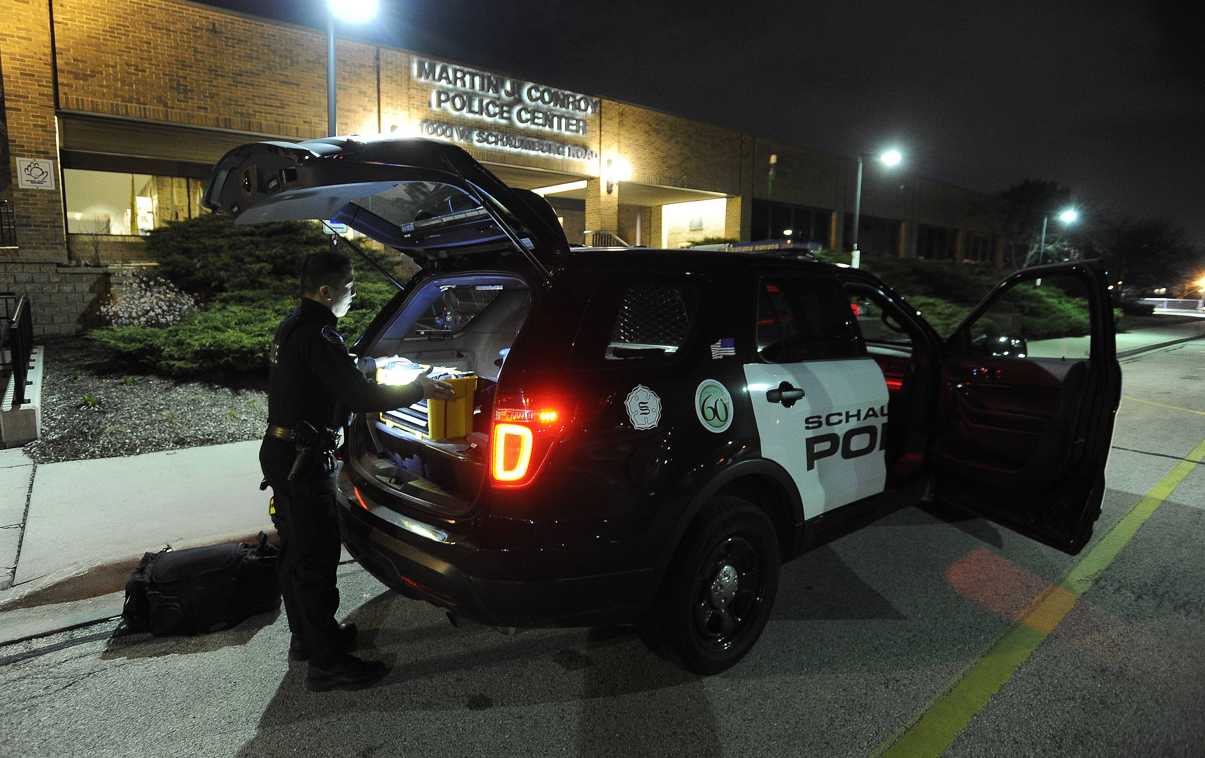 Eric Wang of Chicago, who has been with the Schaumburg Police Department for just under two years, is also a hostage negotiator with the regional SWAT team. In the early morning hours Wang checks his gear as he heads out to patrol the streets of Schaumburg.