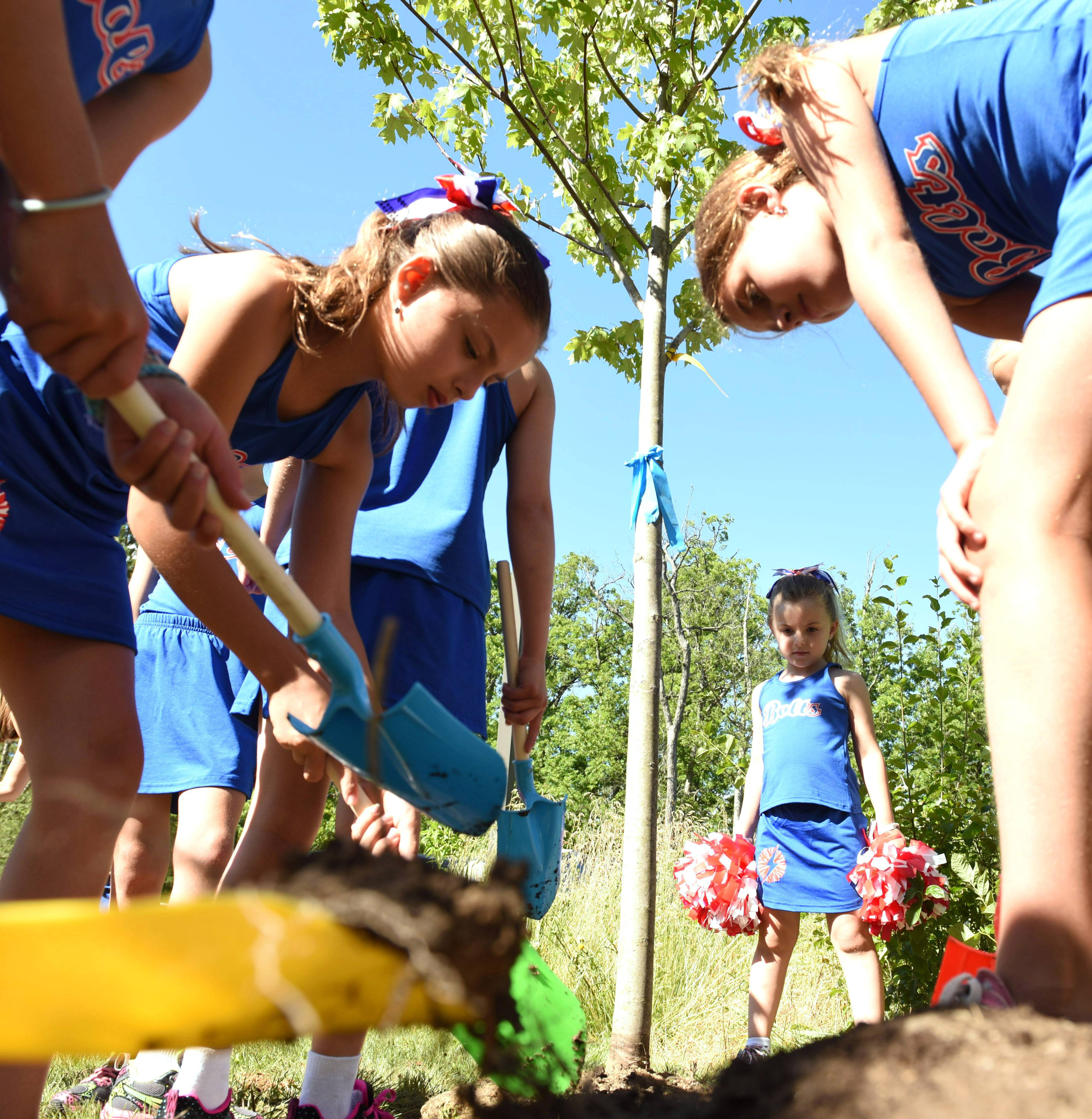 Members of the Lincolnshire Bolts pom squad shovel soil into the hole for a newly-planted maple tree on Monday at the Lutheran Church of the Holy Spirit in Lincolnshire. The group donated a maple tree to the church as a thank you for allowing them to practice there.