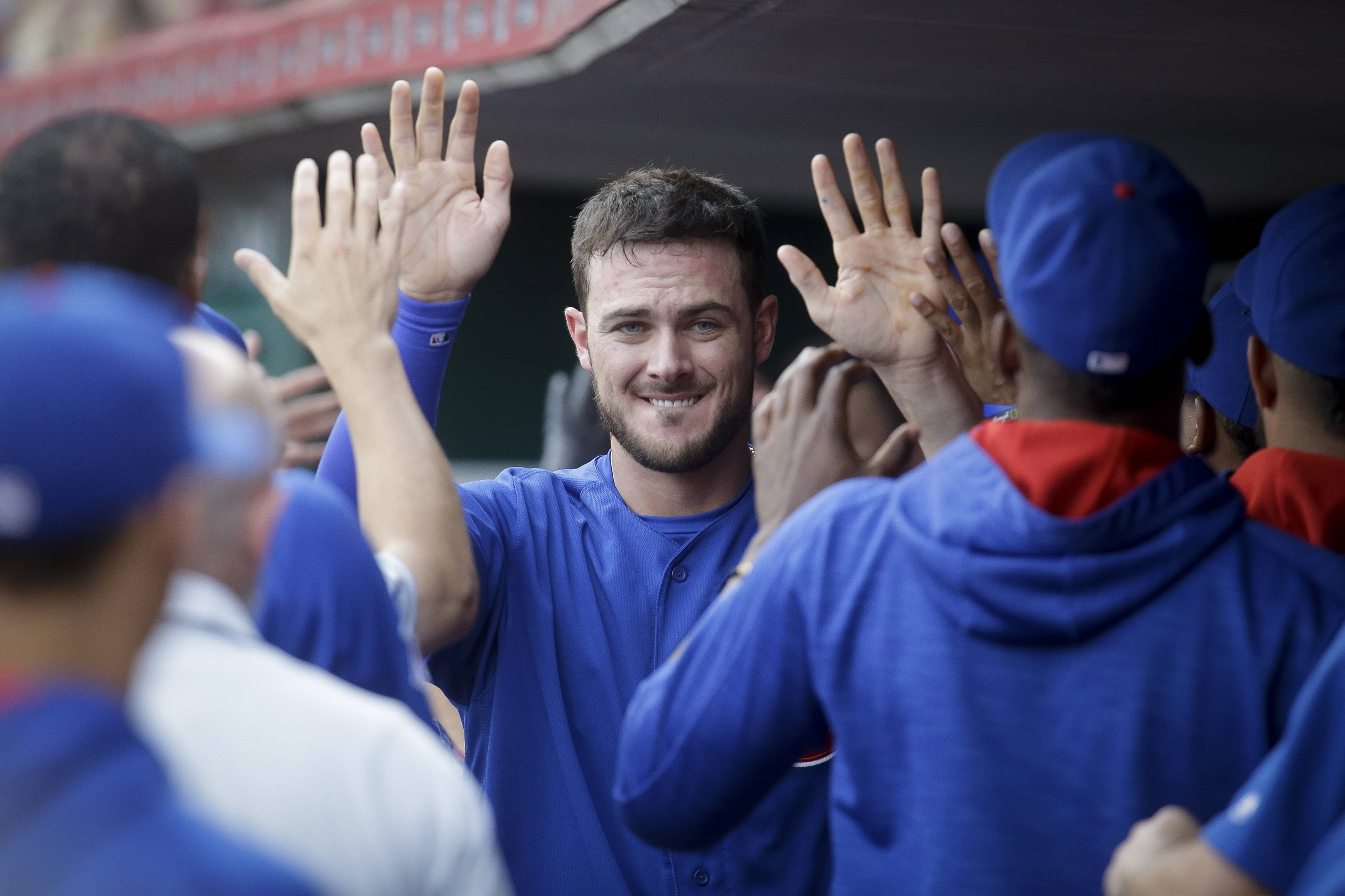 Chicago Cubs' Kris Bryant celebrates in the dugout after scoring on an RBI sacrifice fly by Miguel Montero off Cincinnati Reds starting pitcher Dan Straily in the first inning of a baseball game, Monday, June 27, 2016, in Cincinnati. (AP Photo/John Minchillo)