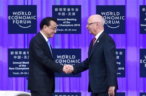 Founder and Executive Chairman of the World Economic Forum Klaus Schwab, right, shakes hands with Chinese Premier Li Keqiang during the World Economic Forum in Tianjin, China Monday, June 27, 2016. (Wang Zhao/Pool Photo via AP)