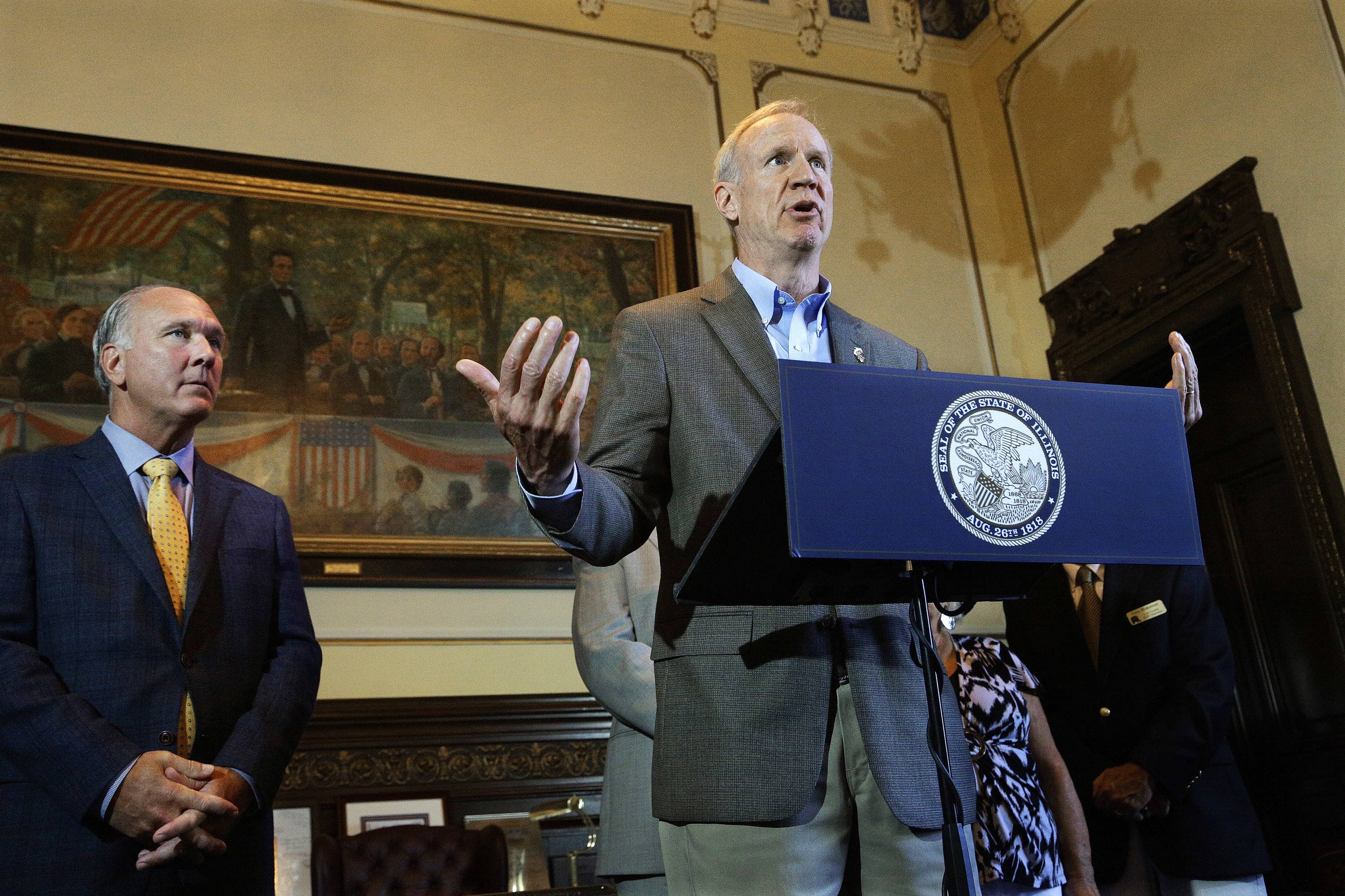 Illinois Gov. Bruce Rauner speaks to reporters Monday about the state budget and education funding in his office at the Illinois State Capitol in Springfield. Looking on is City of Naperville Mayor Steve Chirico.