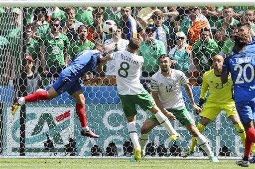 France's Antoine Griezmann, left, scores his side's first goal during the Euro 2016 round of 16 soccer match between France and Ireland, at the Grand Stade in Decines-­Charpieu, near Lyon, France, Sunday, June 26, 2016. (AP Photo/Thanassis Stavrakis)