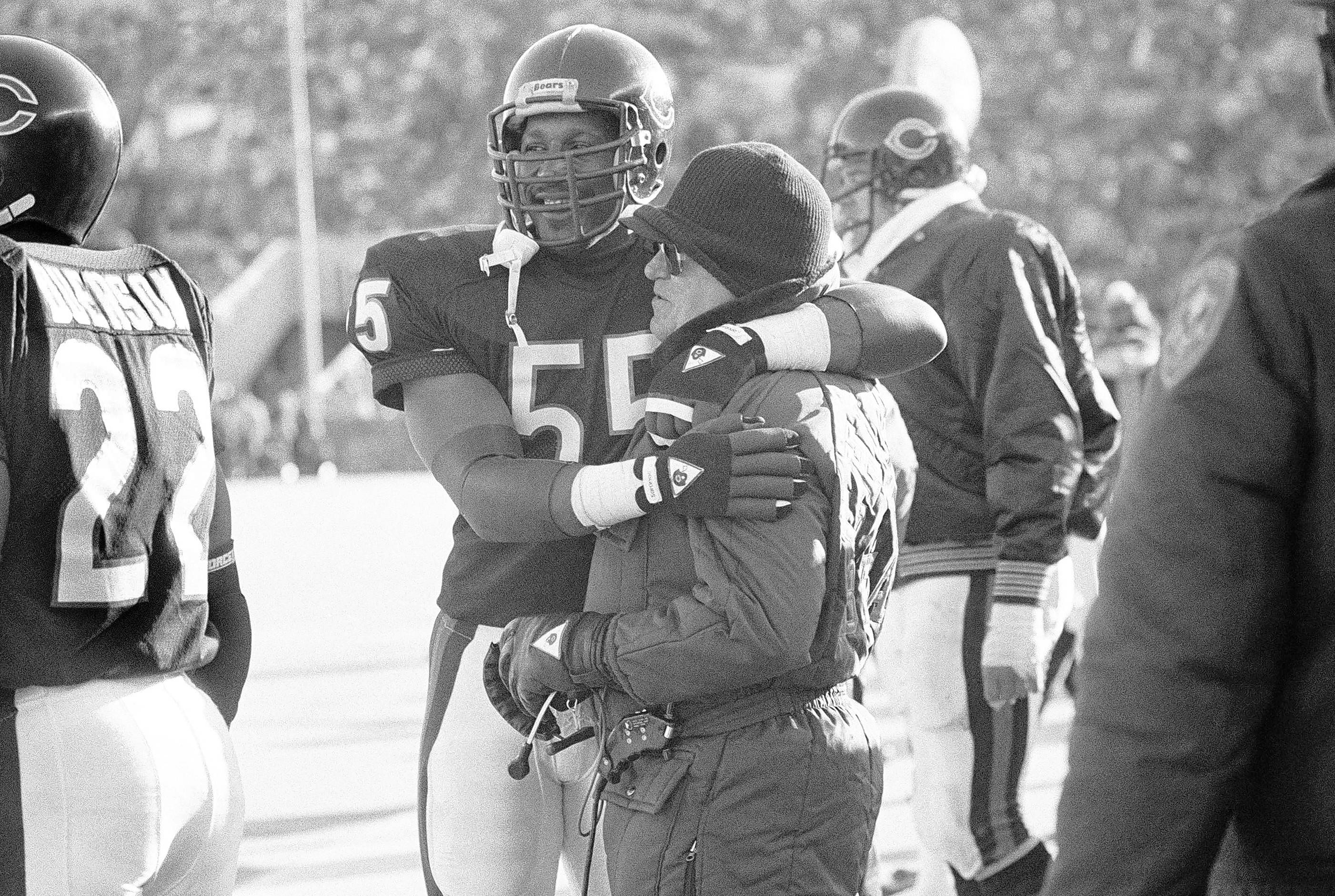 Defensive coach Buddy Ryan of the Chicago Bears hugs linebacker Otis Wilson (55) as they watch the final seconds run off the clock in the Bears game against the New York Giants, on Jan. 5, 1986 at Soldier Field in Chicago. The Bears defense held the Giants 181 yards in the game which sends the Bears against the Los Angeles Rams.(AP Photo/John Swart)