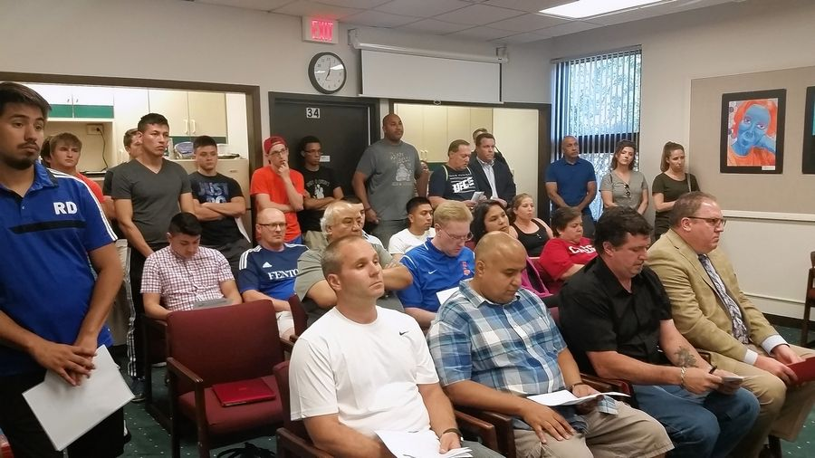 More than 20 people came to a Fenton High School District 100 school board meeting Monday in support of David Alvarez, front row, second from left. Alvarez was terminated this month from his job as IT coordinator and his position as head coach of the boys varsity soccer team at the Bensenville school.