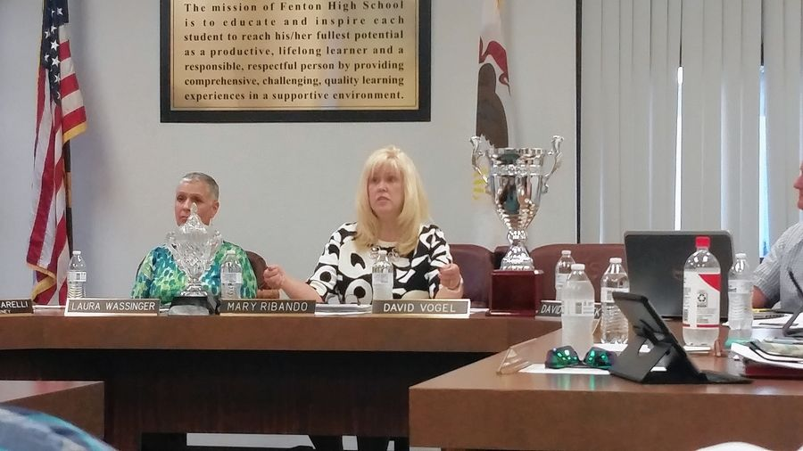 Fenton High School District 100 school board President Mary Ribando motions to two soccer trophies that she brought to Monday's board meeting, noting that the district has always supported soccer in the community.