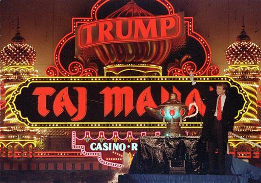 FILE - In this April 5, 1990 file photo, Donald Trump stands next to a genie's lamp as the lights of his Trump Taj Mahal Casino Resort light up during ceremonies to mark its opening in Atlantic City, N.J. Soon after the opening, Trump owed $70 million to 253 contractors employing thousands who built the domes and minarets, put up the glass and drywall, laid the pipes and installed everything from chandeliers to bathroom fixtures. The next year, when the casino collapsed into bankruptcy, those owed the most got only 33 cents in cash for each dollar owed, with promises of another 50 cents later. It took years to get the rest, assuming the companies survived long enough to collect. (AP Photo/Mike Derer, File)