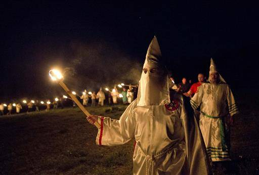 "In this Saturday, April 23, 2016 photo, members of the Ku Klux Klan participate in cross burnings after a ""white pride"" rally in rural Paulding County near Cedar Town, Ga. Born in the ashes of the smoldering South after the Civil War, the KKK died and was reborn before losing the fight against civil rights in the 1960s. Membership dwindled, a unified group fractured, and one-time members went to prison for a string of murderous attacks against blacks. Many assumed the group was dead, a white-robed ghost of hate and violence. (AP Photo/John Bazemore)"