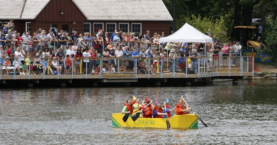 "The ""Crayola 7"" captained by Jessica Mills starts paddling in front of a gallery of onlookers during the Lake Ellyn Cardboard Boat Regatta in Glen Ellyn."