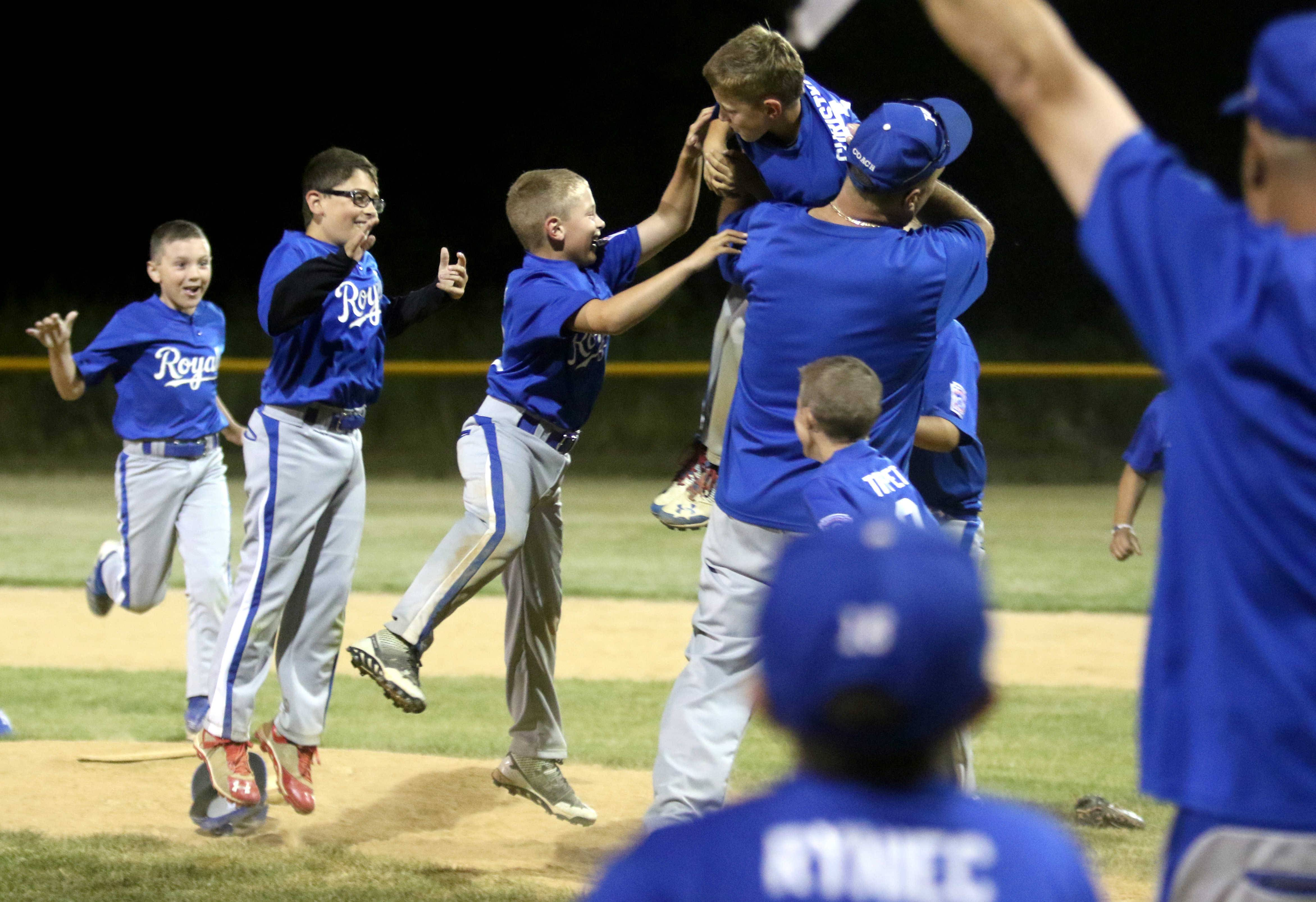 The Bartlett Royals celebrate as they were victorious against the Streamwood Yankees in the Little League Division 13 Minor championship game at Koehler Field in Bartlett Friday night.