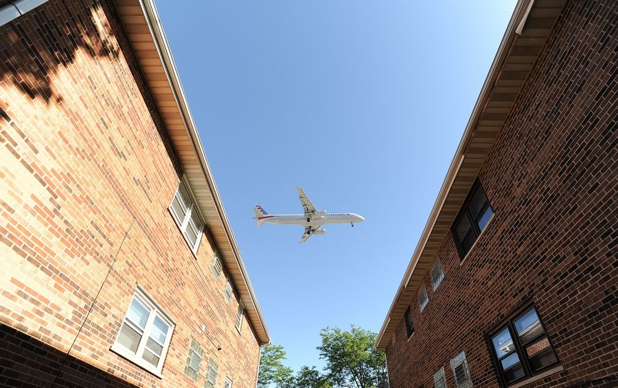 A jet passes over Hillside Drive in Bensenville as it prepares to land at O'Hare International Airport. Officials hope a new runway rotation plan will bring noise relief at night for residents, but some current and former air traffic controllers have concerns.