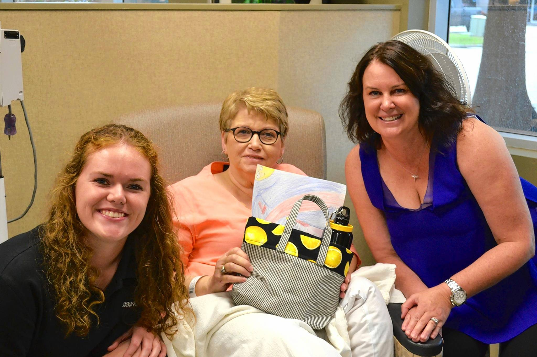 Race car driver Sarah Montgomery, left, and Jill Swanson Peltier, right, deliver a Lemons of Love bag to a cancer patient at an oncology center in Lafayette, Louisiana, where Montgomery is from.