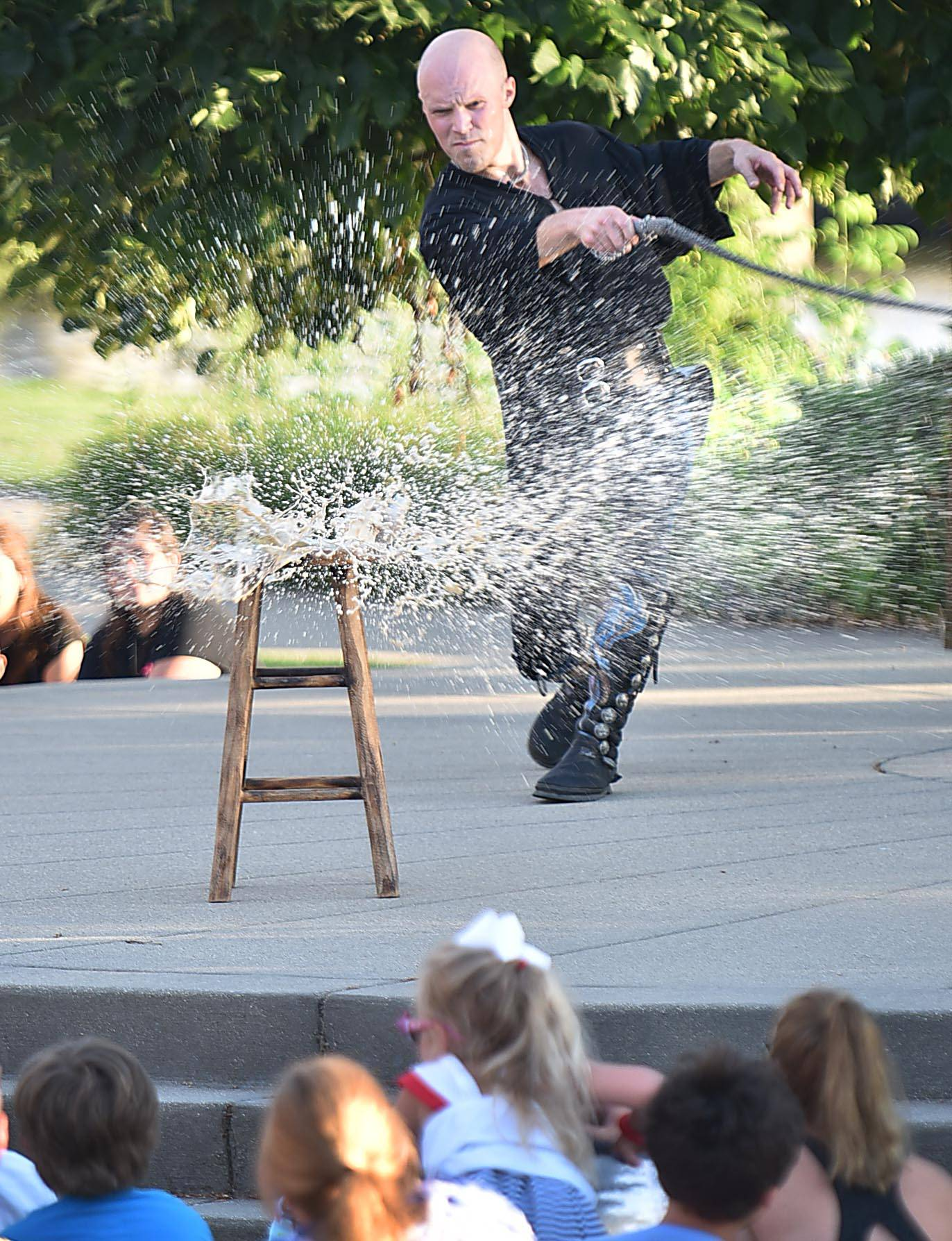 "Performer Adam ""Crack"" Winrich slices a soda can with his whip Monday evening at a family picnic hosted by the Gail Borden Public Library in Elgin. He performs around the world and has set 16 Guinness World Records with his whip."
