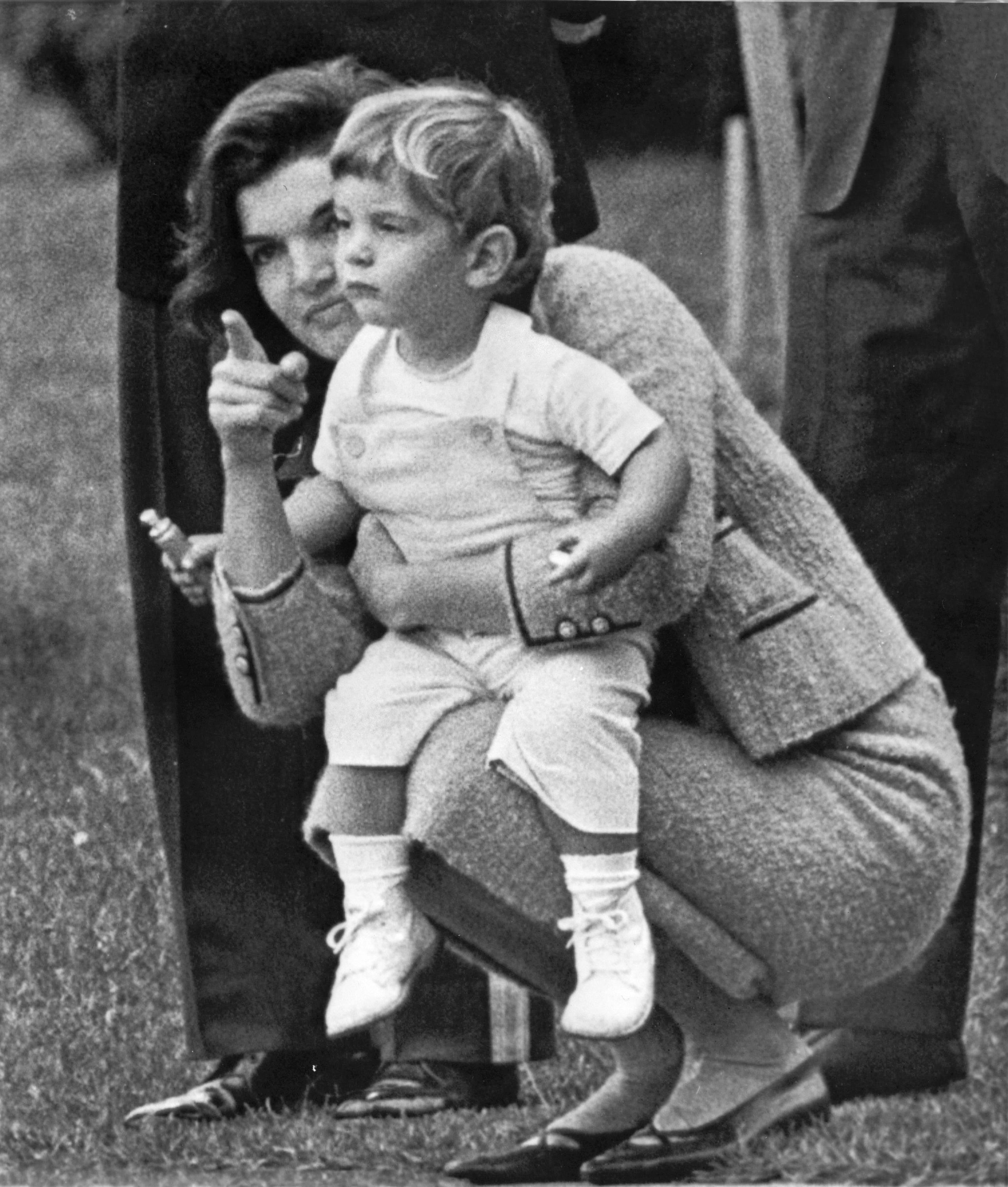 John f kennedy jr watches from the rose garden with his mother