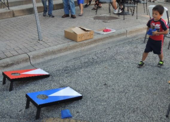 A little tot enjoys the Bean Bag toss at Cruise NIght in Lombard,  Flat apple is open to kids ages preshchool to high school.jaywojcik@ymail.com