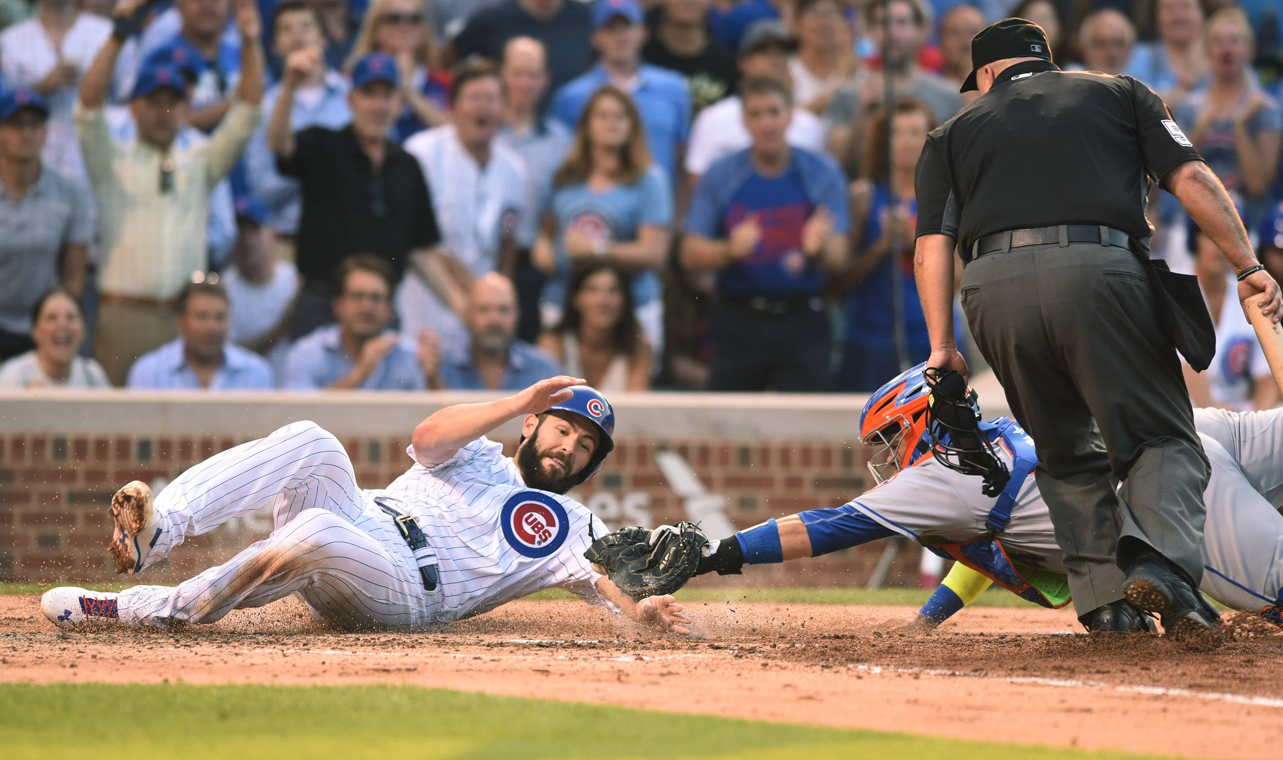Jake Arrieta of the Chicago Cubs gets tagged out at the plate by New York Mets catcher Rene Rivera during the bottom of the fourth inning of Tuesday's game at Wrigley Field in Chicago.