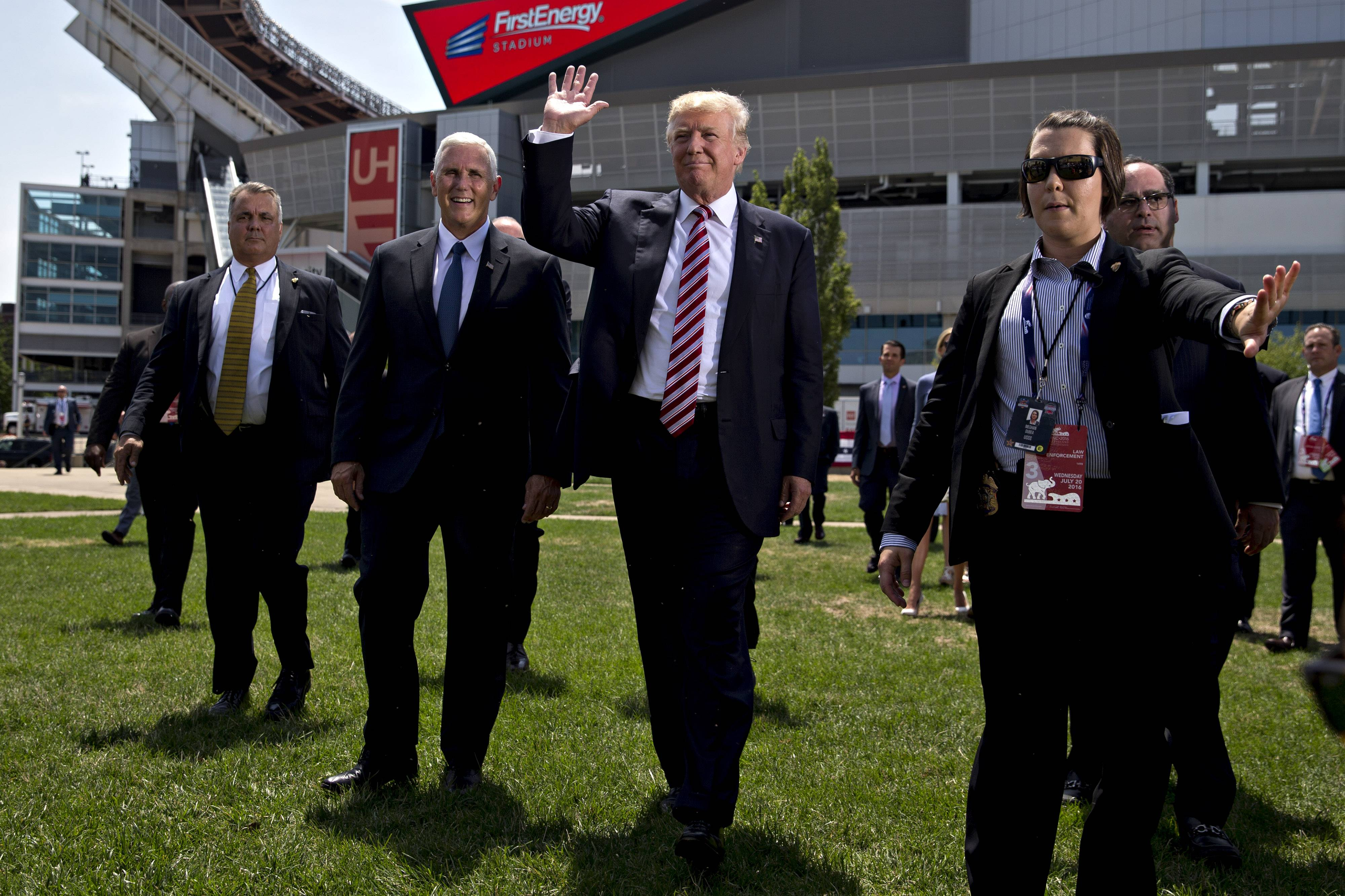 Donald Trump, 2016 Republican presidential nominee, center, waves while arriving with Mike Pence, 2016 Republican vice presidential nominee, second left, during a friends and family event on the sidelines of the Republican National Convention (RNC) in Cleveland, Ohio, U.S., on Wednesday, July 20, 2016. Trump, a real estate developer, TV personality, and political novice, was formally nominated as the 2016 Republican presidential candidate Tuesday night in Cleveland after his campaign and party officials quashed the remnants of a movement to block his ascension.
