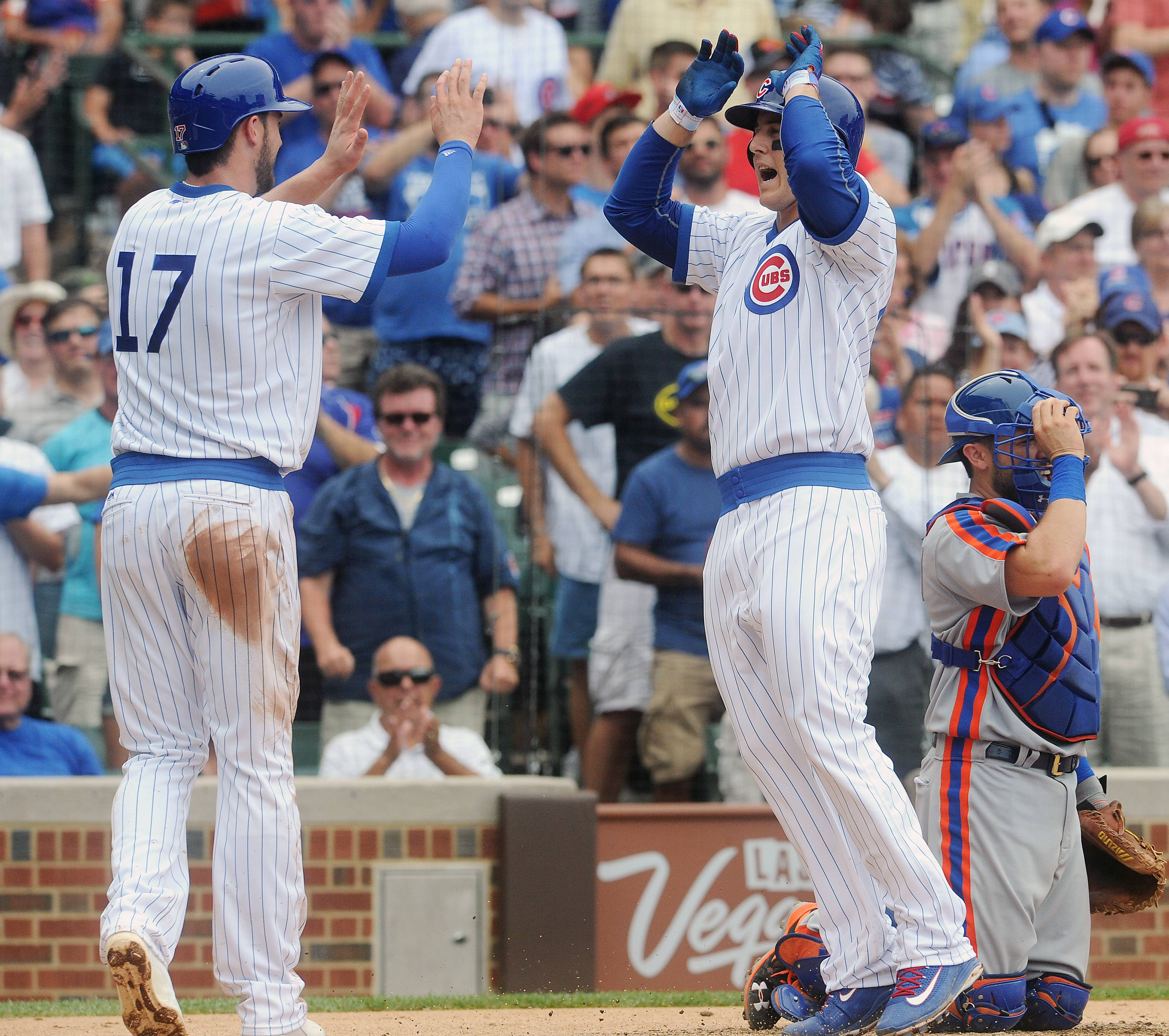 Cubs first baseman Anthony Rizzo is congratulated by teammate Kris Bryant in the 5th inning after his second home run put the Cubs ahead 5-0 against the New York Mets at Wrigley Field.