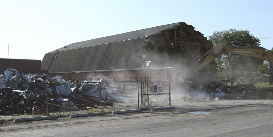 Dust rises as crews from American Demolition Corp. of Elgin tear apart the Barn Recreation Center on Martin Avenue in Naperville on Wednesday morning.