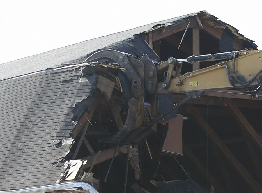 Demolition equipment tears apart the roof of the 51-year-old Barn Recreation Center in Naperville, which is being razed this week to make way for a new central maintenance facility for the Naperville Park District.