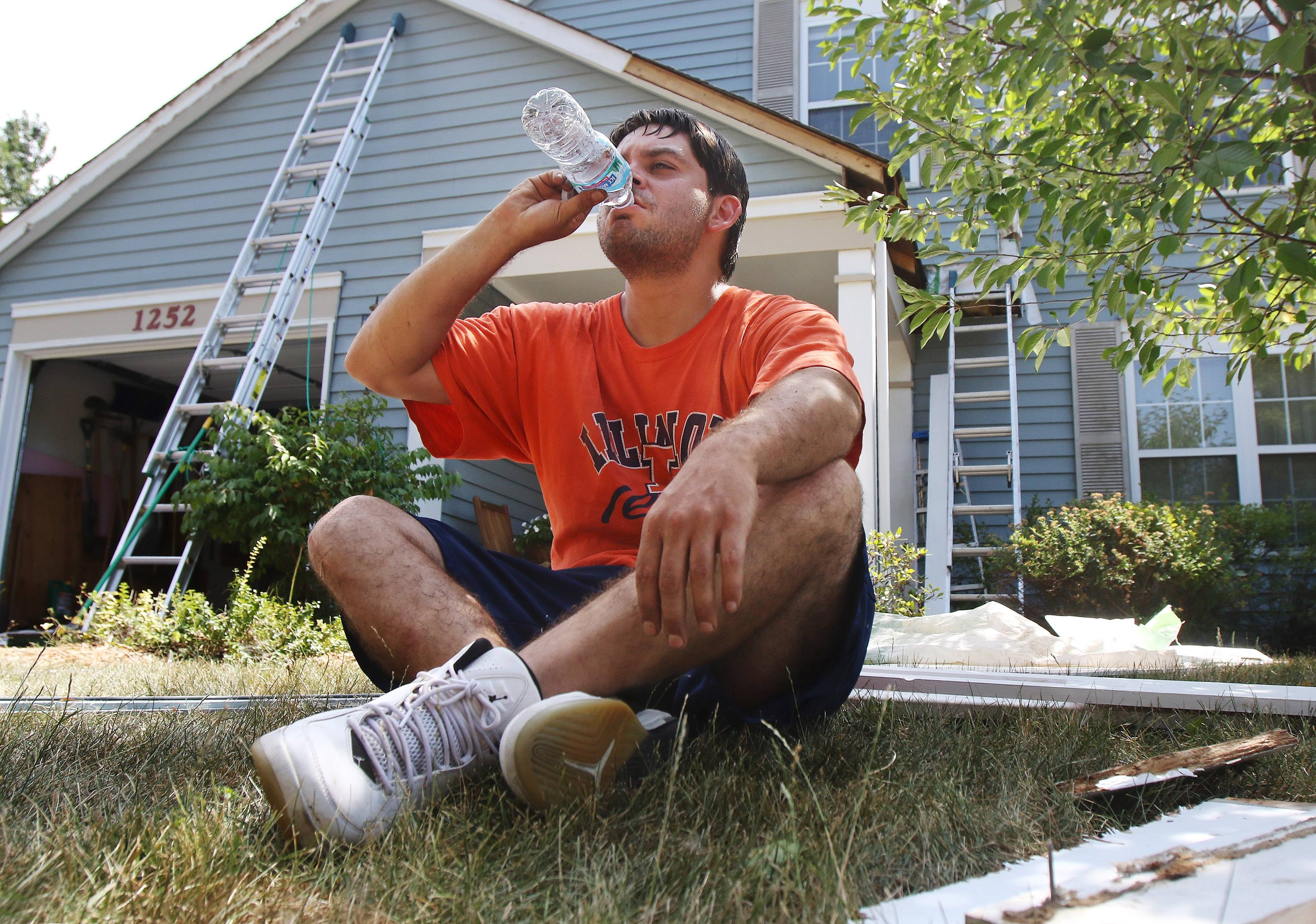 Carpenter Rudy Ayala of Round Lake Beach drinks water while sitting in the shade to keep cool as he repairs a Mundelein house. Temperatures were expected to reach the upper 90s and the heat index was expected to be over 100.