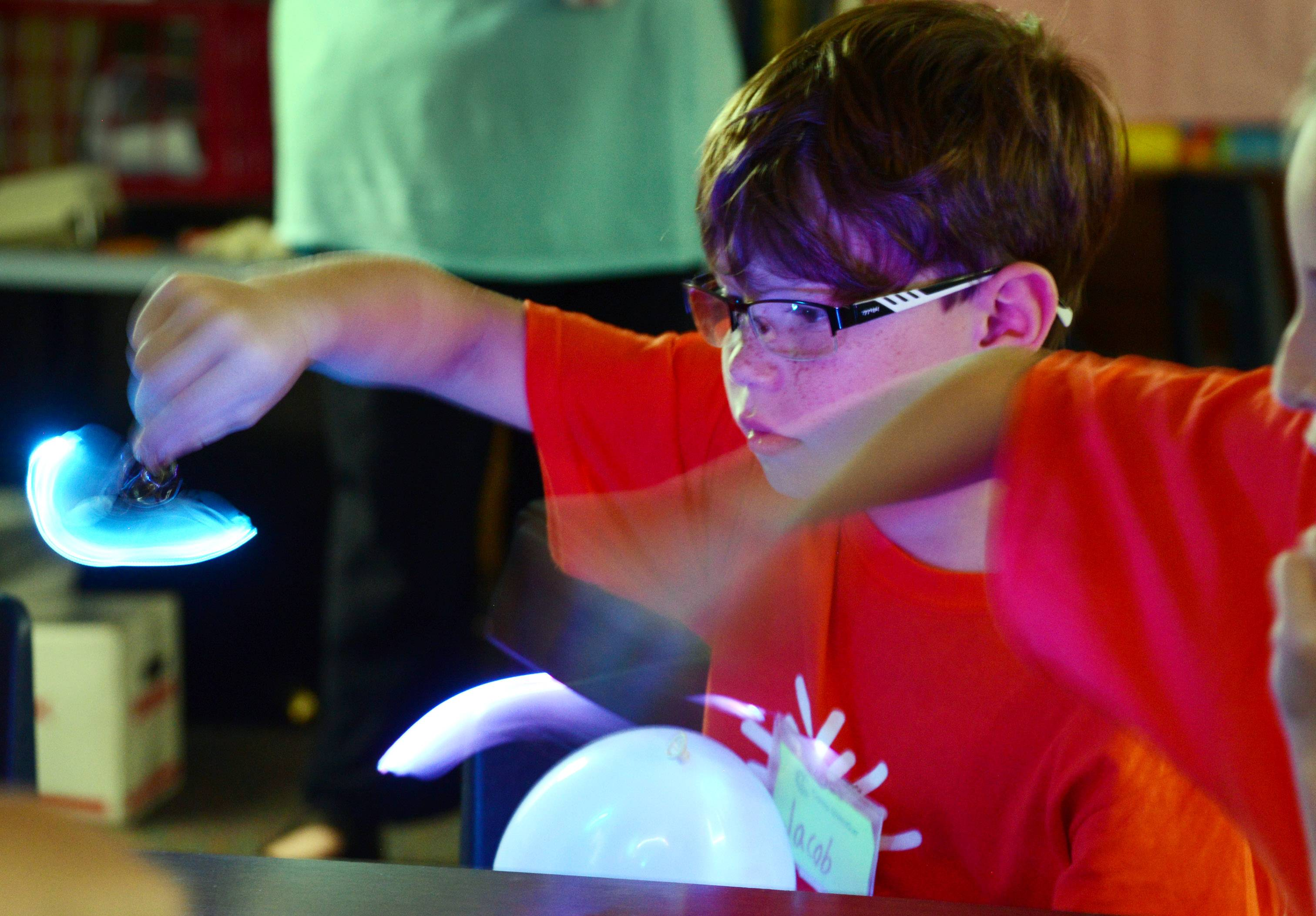 Jacob Whisenand and fellow students play with light sources during the Where Pigs Fly and Anything is Possible session at Rockland School in Libertyville on Friday.